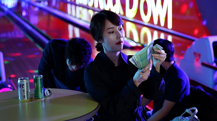 Korean woman counts big money at bowling alley gambling.