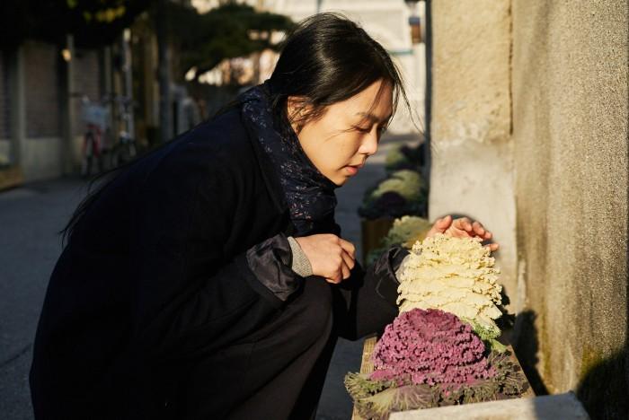 Korean girl smelling flowers in the sunshine.