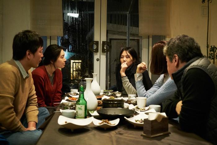 Koreans drink soju and talk over dinner.
